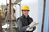stock photo of scaffold  - Construction inspector examine styrofoam insulation of house facade - JPG