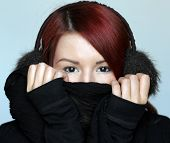 stock photo of muffs  - Redhead girl in fur ear muffs covering her face with black scarf - JPG