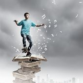 Boy skater standing on pile of old books