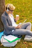 education, technology and internet concept - smiling male student in eyeglasses with tablet pc, take away coffee and headphones outdoors