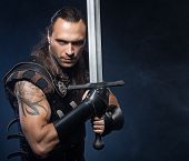stock photo of longsword  - Young man has some dangerous hobby - JPG