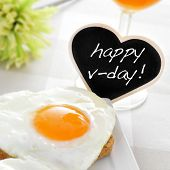 a heart-shaped fried egg on a toast and the text happy v-day written in a heart-shaped chalkboard