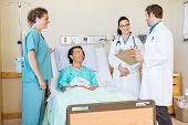 Young doctors discussing report while nurse and patient looking at them in hospital room