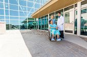 Full length of nurse and doctor looking at patient on wheelchair at hospital courtyard