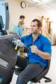 Young man on exercise bike with physical therapist assisting patient in hospital