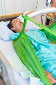 Mature male patient lying on sling of hydraulic lift on bed at hospital
