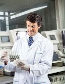 Mid adult male technician analyzing urine samples in laboratory