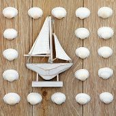 Abstract of cockle shells with small white boat over old oak background.