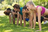 foto of side view people  - Side view of a group of fitness people doing push ups in the park - JPG