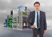 Serious businessman standing with hand on hip against cloudy dull sky