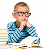 Cute little boy is reading a book while wearing glasses and showing hush sign, isolated over white