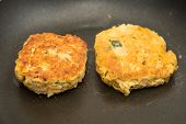 picture of crab-cakes  - Fresh crab cakes browning in hot oil in a pan - JPG