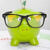 Green Piggy Bank Over Stock Market Chart With 100 Dollars Banknote - Studio Shot