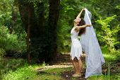 Beautiful barefoot woman in a stylish white dress pose in a forest  of lush green trees