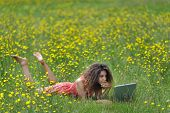 Cute young woman with curly hair lying reading a book in a wildflower meadow full of colorful yellow summer flowers as she relaxes in the tranquility and beauty of nature