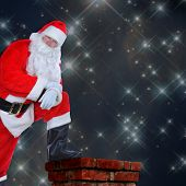 Santa Claus standing on a roof with one foot on the chimney. His arms are folded and he is leaning o