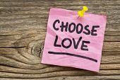 choose love reminder - handwriting on a green sticky note against grained and knotted wood board