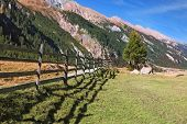 Alpine Valley in Austria. Headwaters National Park Krimml.  Scenic farm fields blocked bythe wooden fence. Steep mountain slopes overgrown with coniferous forests