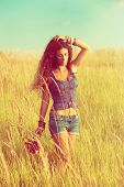 young woman with long curly hair enjoy in walking through yellow summer grass, wearing jeans shorts and boho style top, retro colors