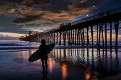 A young surfer sees nothing but flat waves but lingers to admire the colors and reflections near the