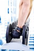 Guy with dumbbells on gym background