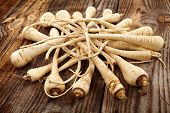 stock photo of parsnips  - Closeup of a bunch of parsnip on a wooden board