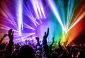 Happy young people having fun on rock concert in nightclub, colorful glowing lights, enjoying popula