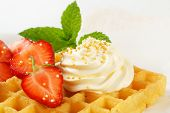 Belgian waffle with whipped cream and strawberries