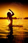 Beauty Model Girl Splashing Water. Teen girl Swimming and splashing on summer beach over sunset. Beautiful Woman Enjoying nature