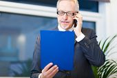 Portrait of a mature businessman speaking at the phone