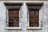 Two Windows On An Old Gray Stucco Wall.