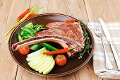 savory : grilled spare rib on dark dish with thyme pepper and tomato on wooden table