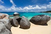 Stunning beach with white sand, unique huge granite boulders, turquoise ocean water and blue sky at