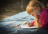 Girl Draws A Pencil On White Paper.