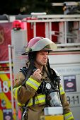 MONTREAL,  CANADA - AUGUST 01: Lieutenant firefighter in front of firetruck on a fire site, talking on walkie on august 01, 2014 in MONTREAL
