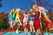 Kids standing in a row on red ropes of playground