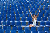 Young Woman Sitting In Stadium Cheering