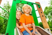 Boy and girl behind hug on chute with smile