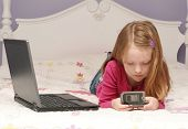 Young Girl using laptop and Cell phone