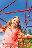Portrait of blond smiling girl on net ropes