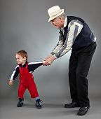 stock photo of discipline  - Grandfather trying to discipline his naughty grandson - JPG