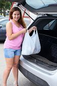 Smiling Woman Loading Shopping Bag In Trunk Of Her Pov
