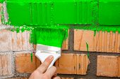 Paint Brush With Green Color On Brick Wall