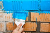 Paint Brush With Blue Color On Brick Wall