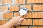 Caucasian Hand Starting To Paint Brick Wall