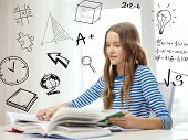 education and home concept - smiling student girl sitting at table and reading books