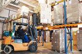 image of forklift  - Worker driver of a forklift loader at warehouse loading cardboard boxes on pallet to shelves - JPG