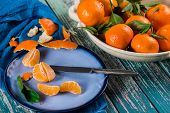Fresh Clementines In Bowl And Peeled On Plate From Above