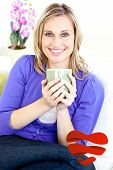 Blond woman enjoying her coffee sitting on the sofa in the livingroom against heart