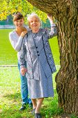 Granddaughter And Grandmother Posing In A Park Near The Tree